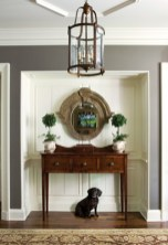 The Ansleys' Boykin spaniel, Bodie, spends most of his time in the foyer of their new home. Mirror, Peridot Antiques, Savannah. Sideboard, The Englishman Fine Art & Antiques. Chandelier, Edgar-Reeves. Paint color, Benjamin Moore Oyster Shell.
