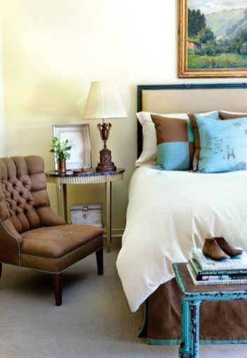 """In the master bedroom, pillows in a blue-and-brown """"Manchu"""" print by Osborne and Little play off the blue of a rustic bench. Fabric available through Grizzel & Mann, ADAC, (404) 261-5932. Regent iron headboard, PierceMartin, ADAC, (404) 495-9329."""