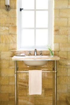 """Onyx-lined walls in the bathroom are instantly eye-catching, with minimal fixtures that don""""t interrupt the effect in the least."""