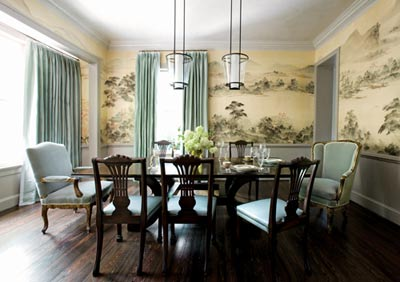 """""""I saw this wall covering and told the homeowner that she had to keep it,"""" says Steinfeld. """"It's so special and I knew we could modernize it."""" The clients' own dining chairs now team up with antique host and hostess chairs, all tied together with the same watery blue hue. Above the McGuire table, the designer used Holly Hunt light fixtures that have an Asian influence. """"If we start out traditional in a room, I want to put in something contemporary,"""" Steinfeld says, """"and if we start out contemporary, I want to put in something traditional."""" Drapery fabric, Great Plains silk through Jerry Pair."""