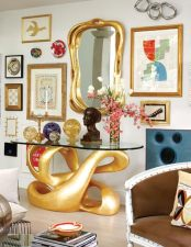 A biomorphic console and mirror is a Tony Duquette original—one of four—which came from the dressing room of his estate. It is surrounded by the works of Koons, Lichtenstein, Picasso, Warhol and even Oetgen (bottom right). The orbs and bust are made of cracked Lucite.