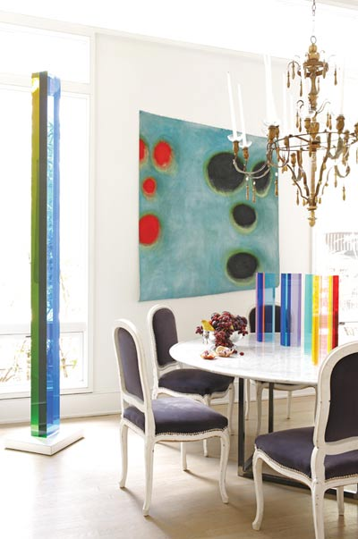 In the dining room, acrylic sculptures by Vasa Mihich and a canvas by Oetgen are in striking juxtaposition to an antique Italian chandelier and a set of painted dining chairs that he acquired through Sotheby's.