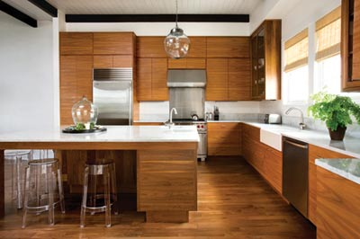 """The kitchen was unfinished when Musso and Cooke purchased this home, giving him free reign to design the cooking space of his dreams. Using a local Florida cabinetmaker, he had walnut cabinetry constructed in a clean, streamlined style. """"All of the wood is cut from the same sheet, so the grain extends linearly across the whole room,"""" says Musso. """"It""""s just a really simple, functional look""""light, airy and great to cook in. I actually love it more than my kitchen at home."""""""
