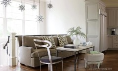 At one end of the kitchen, a casual eating area proves that even something informal can be luxe. A banquette-style sofa and metal side chair pull up to a limestone-topped table, with a small round ottoman providing more tuck-away seating.
