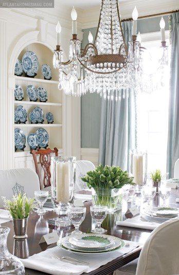 The stylish table setting in the dining room features glass hurricanes and crystal stemware by William Yeoward. Greenleaf china by Anna Weatherly, one of the many patterns Elsey has collected over the years, is set upon custom linens, their monograms matching those of each slipcover. A display niche featuring Chinese porcelain plates from Jane Marsden Antiques is further evidence of Elsey's passion for delicate tableware.