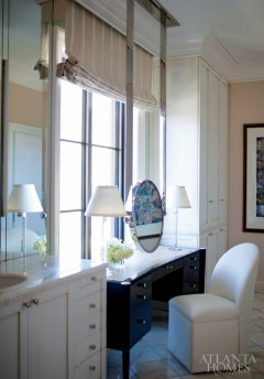 In the master bathroom, a J. Robert Scott black lacquer desk serves as a vanity. A mirror is suspended from the ceiling and is flanked by Downsview cabinetry. Slabs of white onyx from Walker Zanger were used for the countertops, and white onyx tiles from Artistic Tile were used for flooring.