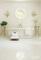 In the pristine master bath, a Waterworks tub floats amid square tiles of Thassos marble and pure white walls.
