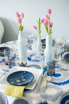 """Quince salad plate, $5.99; Square dinner plate, $4.99; Stainless flatware, $3.99 per piece; Wine glass, $3.99; Etched blue glass with gold detail, $3.99; Chartreuse napkin, $9.99 for eight; All available at Cost Plus World Market, 3330 Piedmont Rd. NE, Atlanta 30305. (404) 814-0801; world-market.com. """"chana"""" fabric for tablecloth, No. 9 Thompson by Jim Thompson, available through—Jerry Pair. Blue bottles, available through Hollyhock, Los angeles glass and metal orbs, available at cb2, 1080 peachtree st. NE, Atlanta 30309. (404) 894-3763; cb2.com Wall color, Palladian Blue by Benjamin Moore"""