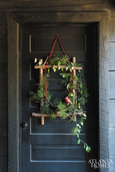 Frame of white pine branches and boughs, evergreen honeysuckle, red velvet ribbon and carved red bird, from $145.