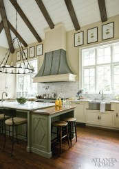 Ceiling beams and walls of windows provide plenty of eye candy in the kitchen; Morris simply added small touches such as the watercolor egg prints from Ainsworth-Noah & Associates and a rugged torch-style chandelier to freshen the space.