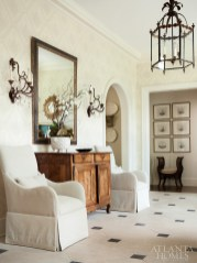 The house's original limestone floor greets visitors in the entry hall. Linen-covered armchairs flank an antique walnut buffet while a subtle wallpaper adds dimension.