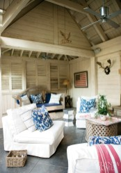 Throw pillows covered in a Clarence House blue-and-white fabric add bold color to the cozy seating area in the pool pavilion. The Pearces have collected hunting trophies and antique flags through the years.