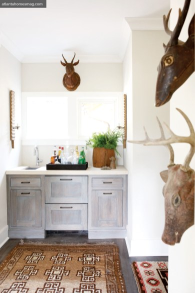 Bell Custom Cabinetry designed the cabinets in the bar area. Large rug, Sullivan Fine Rugs. Small rug, Keivan Woven Arts. Carved deer heads, A. Tyner Antiques. Sconces, tray and wood planter, Bungalow Classic.