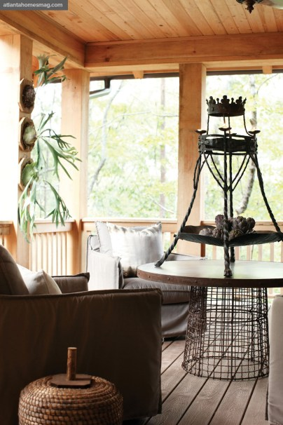 Perched in the forest like a treehouse, the porch overooks a lake. The swivel club chairs are covered in a waterproof fabric. All furnishings, Bungalow Classic. Staghorn ferns available through Garden at White Provision.