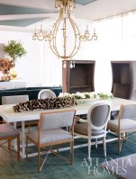 A French gold finish and rock crystals on the Athena Chandelier add a glamorous touch to the dining room. Surrouding the table are a mix of chairs: two upholstered Giselle Host Chairs; four Parker Dining Chairs with oatmeal boucle seats and a pair of Remy Armchairs in cream, upholstered in taupe leather. The floral Composition features a cocoa branch placed atop the Patrick Dining Table. All of these furnishings are available through Bradley Hughes.