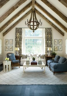 """In the great room, a bird motif on F. Schumacher""""s """"Chenonceau"""" fabric alludes to the forest beyond without distracting from the view. A Hickory Chair sofa is upholstered in outdoor fabric by Nobilis. The wicker chair and two Baker occasional chairs don Pierre Frey acrylic outdoor fabrics, which are available through Travis &""""Company. Driftwood lamps, bird prints and all other accessories available through Mrs. Howard. The room is anchored by a hemp rug with a diamond pattern, which lays atop slate floors."""