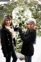 "Daughters Eva (left), a college student and Grace, a middle schooler, ""are never too old to make crafts for the tree,"" says Erica; the two covered the evergreen with ""glittified"" strands of popcorn"