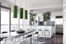 """The kitchen of this Sovereign residence was already imbued with finishes in blue undertones, so Kleinhelter """"whited-out"""" the backdrop and layered green and blue hues throughout the space. Green cylinder pendants, chrome-and-wood dining chairs, a steel X-base table and Lucite-and-chrome bar stools and hide rug from Pieces."""