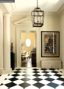 A classic black-and-white marble floor is the perfect complement to the foyer's grand architecture. Lantern, Jerry Pair & Associates. The paint color in both rooms is Urban Putty by Sherwin Williams.