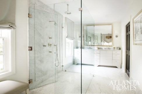 12. A glass shower disappears among the white marble-covered master bath designed by Amy D. Morris. A gilded mirror holds court above his and hers vanities, adding an elegant touch.
