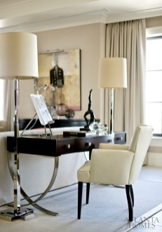A stylish Century desk and Mariette Himes Gomez chair, illuminated by a pair of dramatic floor lamps, fashion an efficient home.