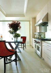 """He describes the kitchen as a """"little jewel box,"""" complete with a sparkling glass wall that allows more light to filter into the space. Kitchen floral designs by Jackson Durham."""