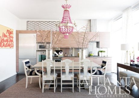 """The Maharani pink chandelier from Redefined Home Boutique sets the mood in the cheerful combination kitchen-and-dining area. Redefined Home Boutique also provided the room""""s gracious dining table, side chairs and bench, as well as the dazzling mercury glass hurricanes and antique grate. The appliances are by Gaggenau."""