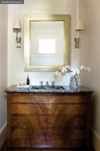 """Howard often converts antique commodes into vanities. In this home""""s powder room, an antique chest with its original granite top holds a new Waterworks hammered metal sink."""