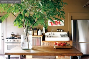 "Even in the kitchen, Paul""s subtle balance between high and low is evident, from the Bertazzoni Italian range and Bosch dishwasher to the crafted cabinets from repurposed pine planks. The vintage Tab sign was a gift from Harris. ""We tried to make it as livable as possible,"" Paul says."