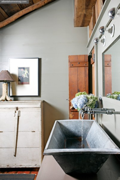 "Ever resourceful, Paul transformed a salvaged trough into a refined sink basin in the bathroom; the wooden door was reclaimed from an Atlanta neighbor""s home being torn down."