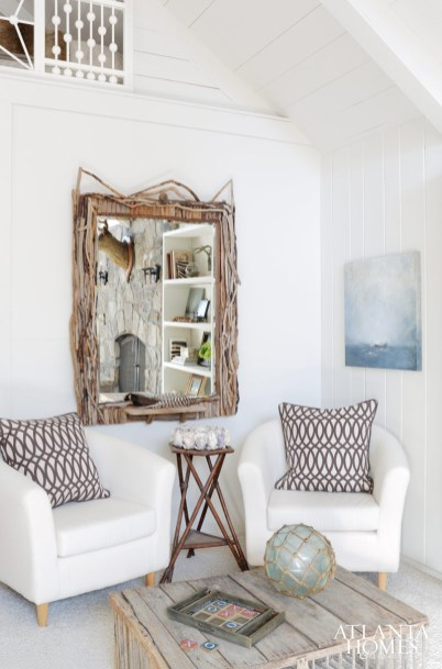 This collected corner of the family room offers a nod to lakeside style with a handcrafted twig mirror by a local artisan, a painting by Raulet Hall, bucket chairs from IKEA, accent pillows from Villa Home Collection and a chicken coop-turned-coffee table.