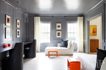 """In the study, pairs of overscaled pieces create a """"simplified, harmonious, yet practical environment for a young family,"""" says Douglass. """"The use of strong colors as accents around purposeful upholstery pieces pulls together the modern with the old."""" The chaises, woven desk chairs and orange stools are from South of Market. The owners' collection of color photography features works by artist Stephen Wilkes, which are set against lacquered walls painted in Pratt & Lambert's London Fog."""