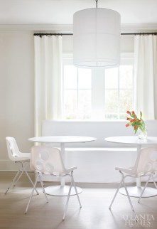 In the breakfast room, an upholstered banquette is paired with modern pedestal tables, vintage chairs from France and an overscaled drum pendant light fixture.