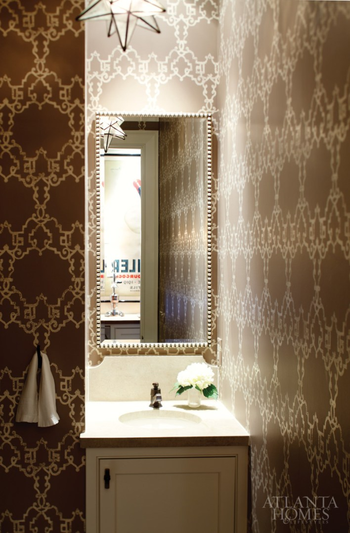 Situated opposite the wet bar, a powder room features an Arabesque-patterned Nina Campbell wallpaper-one of the only patterns in the home. It's accented by the geometric lines of a white-glass Moravian star pendant and a sculptural limestone countertop.