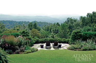 """To take full advantage of the breathtaking views, designer John Oetgen extended the home's covered porch with a half-round that can accommodate a table for 10. """"The gardens all around the house are extraordinary,"""" says Oetgen, noting that Jeremy Smearman from Planters, Inc., was in charge of it all. """"There's every variety of conifer you can imagine."""" The chaises are ideal for taking in the undulating countryside—there are mountains and valleys as far as the eye can see."""
