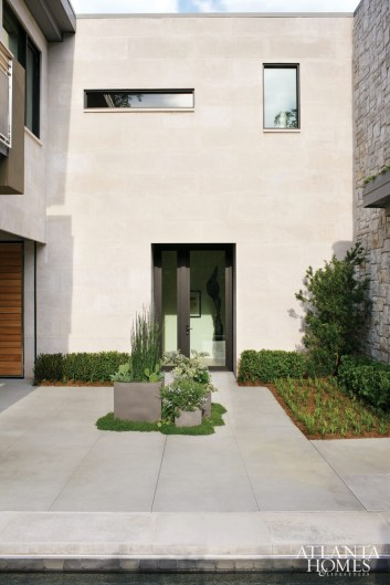 Georgia granite and limestone-materials Cummins and Tavel had seen while strolling the Ansley Park neighborhood-were selected for the home's exterior. Groupings of planters serve to soften the edges of this modern home.