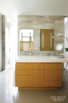 A polished limestone wall in the master bath references limestone used on the exterior. TaC Studios designed the mirrors and cabinetry. Cabinetry, Block and Chisel. Counters, Silestone.