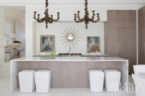 A pair of chandeliers by Oly take center stage in the expansive kitchen island.