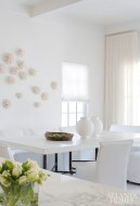 A pair of concrete-topped tables by Bradley are pushed together to seat 16 people comfortably in the dining area. Lee Industries chairs are covered in white pleather. A collection of coral appears to drift into a current across the wall.