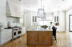 A lime-washed oak island anchors the sprawling whitewashed kitchen, lined in custom cabinetry by Block & Chisel and outfitted with Calcutta Gold countertops and an eye-catching reclaimed barn wood range hood.