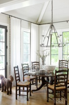 A Jerry Pair iron chandelier centers the vaulted ceiling in the window-wrapped breakfast nook. Dishes by Match and a Formations bowl from Jerry Pair top the family's heirloom table surrounded by Holland & Company chairs.