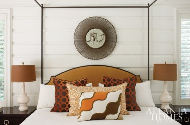 A pile of accent pillows from Bungalow Classic punctuates the Mrs. Howard iron bed with upholstered headboard in the master suite. The bed is flanked by Thomas O'Brien bedside chests.