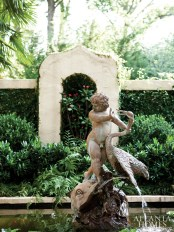 Providing a focal point in the lower courtyard is a bronze fountain with a classical theme—an infant warding off a large bird—while a Crown of Thorns tucked into a niche affords an ever-blooming backdrop.