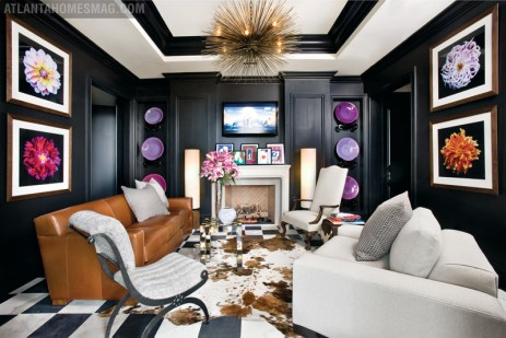 """""""I wanted this room to feel big because it's not; it's little,"""" says Oetgen. """"That's why I painted it black, because you have no boundary edge with black."""" A saddle leather sofa anchors the comfy fireside seating group. Flower photographs by Murphy Townsend. Jean de Merry chandelier through R. Hughes."""