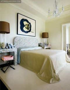"""This room's understated elegance is due, in part, to the fact that Oetgen used just one pattern throughout a subdued paisley found on the window treatments as well as the headboard and upholstered bedside tables. The master bedroom is glamorous in an understated, European way. """"The bed isn't piled with millions of pillows; it's just simple,"""" says Oetgen."""