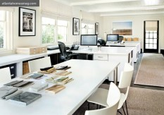 The light-filled work space, which runs the length of the cottage, features white laminate tables, textured linen Roman shades and just a touch of color via framed photographs by Phil Grossman.