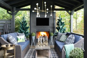 Following dinner, guests gather on the covered porch, which feels even cozier thanks to an outdoor fireplace, throw blankets and propane-powered heaters. Sculptural forest-green trees were made from shipping pallets. Dining table, chairs and braided sisal rug, hayneedle.com. Stacked stone facade, Porcelanosa. Brass chandelier, Grey Furniture.