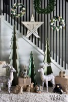 Flynn designed the upholstered Christmas tree sculptures with two interlocking pieces for easy assembly and storage during the off-season. The North Star made from white-washed shipping pallet planks adds graphic interest. The yarn-covered deer is by Alaidriale Derway.