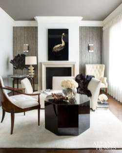 The sitting room, located off the entry hall, sets the tone for the home's subtle elegance with warm tones, tailored upholstery and dramatic details from floor to ceiling. Sconces by Circa Lighting. Art above the mantel from Holland & Company.