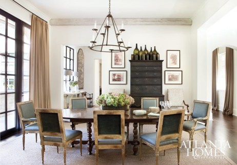 In the dining room, a set of chairs upholstered in Great Plains fabric sidle up to a stately oval dining table by Dennis & Leen. A collection of glass bottles rests atop a dark McAlpine Home highboy from Macrae/Holland & Company.